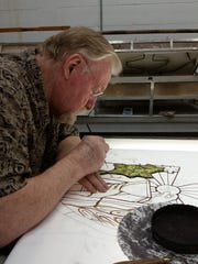Ron Dixon works on a light table to paint leaves on green glass, which will be fired in the kilns behind him. The window is one of two that will be installed in the sacristy of Saint Francis Catholic Church in Staunton in September.