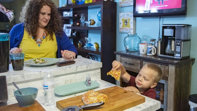 Crystal Camacho finishes her dinner at the kitchen counter as her 4-year-old son, Elias, grabs a second helping of pizza on June 30 at their home in Swannanoa. Before finding a new day care, Camacho and her husband had to take turns staying home half or take their kids to work with them.