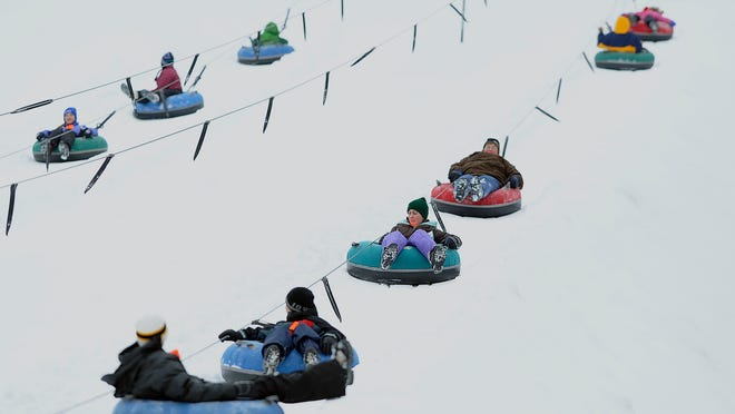 Snow tubers headed up the hill on a rope tow Saturday, Dec. 21, 2013, at Powers Bluff Winter Sports Area in Arpin.