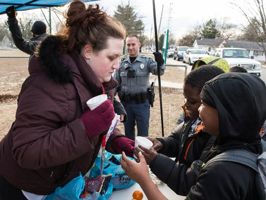 Courtney Armstrong distributes warm beverages to children
