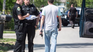 Police investigate a scene near the intersection of N. Turner Street and E. Waid Ave Friday afternoon after a van took off with an officer on the side during a traffic stop near the Muncie Area Career Center on Elgin Street. Three people including the officer were injured.