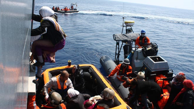 German Navy soldiers help migrants in rubber dinghies to board the German Navy's frigate 'Hessen' following a rescue operation at an unspecified location in the Mediterranean Sea on 06 June 2015. The migrants were brought aboard the Germany Navy's frigate 'Hessen', which brought them to the port of Palermo, Sicily, Italy on Sunday.