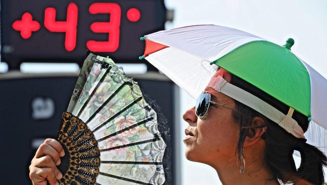 A woman fans her self to cool down as temperatures reach 43 degrees Celsius (109 degrees Fahrenheit) in Florence, Italy, on Aug. 7, 2015. The year will almost certainly be the Earth's hottest on record.