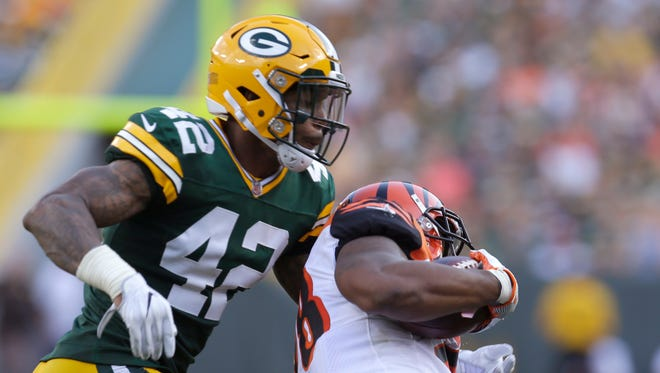 Green Bay Packers safety Morgan Burnett (42) tackles Cincinnati Bengals running back Joe Mixon (28) after a 9-yard gain during the second quarter of their game Sept. 24, 2017, at Lambeau Field.