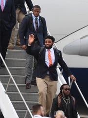 Clemson defensive lineman Christian Wilkins waves as he departs the plane with the rest of the team at Tampa International Airport on Friday, January 6, 2017 for the National Championship game against Alabama on Monday.