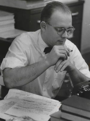 Gerald Kloss pauses with a cigarette, pondering a sentence while writing on a typewriter, in The Milwaukee Journal newsroom in 1957.