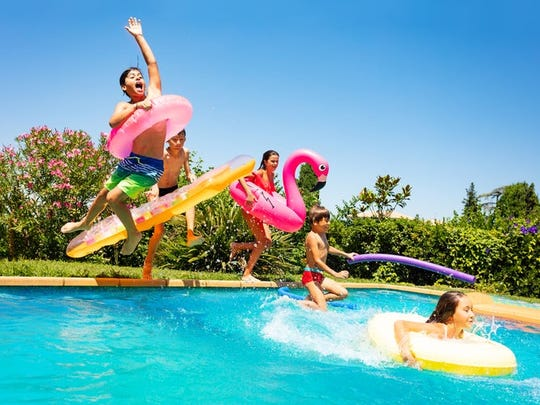 Five younger kids -- three boys and two girls -- with inner various inner tubes/floats jumping in an inground swimming pool.