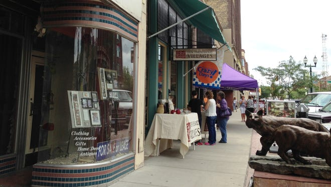 Shoppers browse the table outside Ten Thousand Villages along Phillips Avenue.