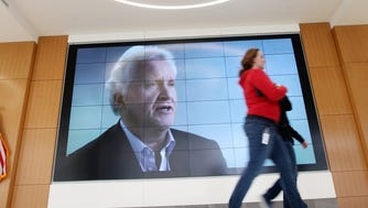 Employees walk through the lobby of  the new General Electric Global Operations building, downtown, where a large screen displays companys products and other images, including that of company CEO Jeffrey R. Immelt.
