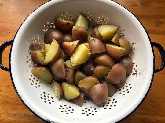 Red-skinned potatoes are cut into bite-size pieces before cooking.