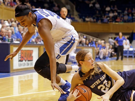 Notre Dame's Madison Cable (22) falls to the floor as Duke's Amber Henson reaches for the ball during the first half of an NCAA college basketball game in Durham, N.C., Monday, Feb. 1, 2016. (AP Photo/Gerry Broome)