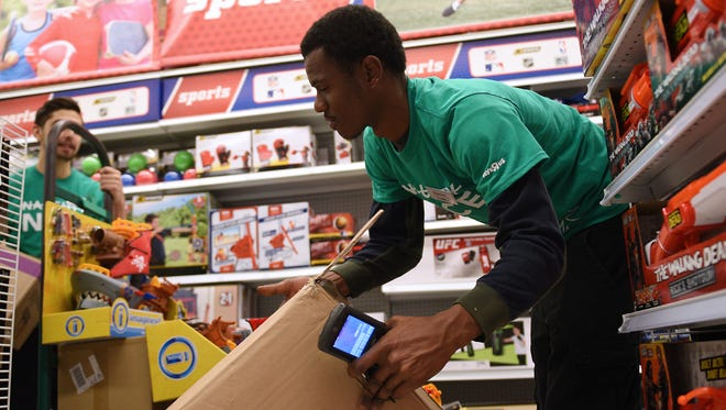 The Toys R Us in Totowa is one of the frontlines where the fight to win Christmas will be fought. Here (from left) Muhammad Asatrian of Woodland Park and Damier Hansford of Paterson unload fresh merchandise and put it on the shelves.