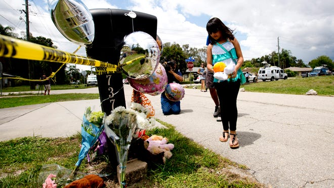 Alondra Vara, 10, places three teddy bears at the home of a family that was killed in a murder suicide in San Carlos Park.  Vara says she was friends with one of the victims, Alison Navas,10.