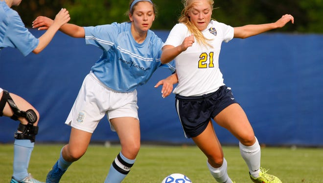 Dewitt's Mackenzie Dawes, right, and Lansing Catholic's Kate Burns battle for the ball Tuesday, May 17, 2016, in DeWitt, Mich. DeWitt won 2-0.