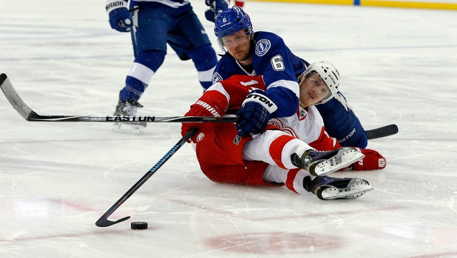 Detroit Red Wings' Gustav Nyquist, front, is checked by Tampa Bay Lightning's Anton Stralman, also of Sweden, during the third period of an NHL hockey game Friday, March 20, 2015, in Tampa, Fla. The Lightning won 3-1.