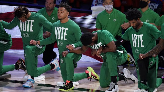 Members of the Boston Celtics lock arms as they listen to the national anthem before an NBA conference final playoff basketball game against the Miami Heat in Lake Buena Vista, Fla.