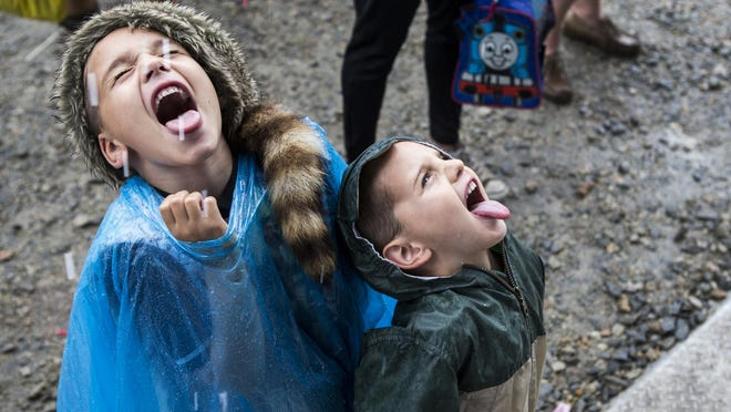 Six year-old Liam and and his brother four year-old Nick Lafferty, of Wilmington, catch rain drops on their tongues near the Main Stage at the Big Barrel Country Music Festival on Saturday.