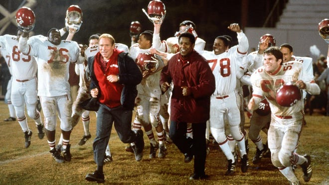 "Will Patton, center left, as coach Bill Yoast and Denzel Washington, center right, as coach Herman Boone star in ""Remember the Titans."""