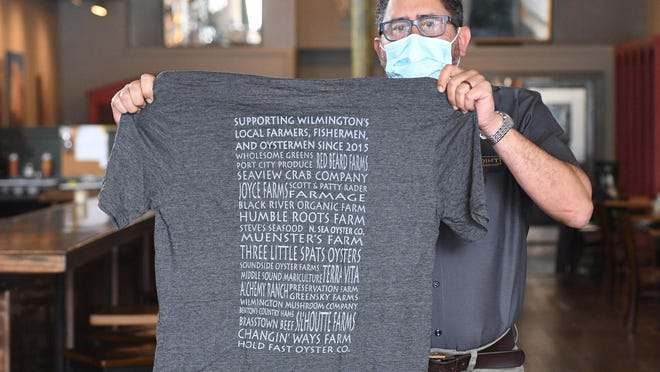 Pinpoint restaurant General Manager Luis Rodriguez holds a t-shirt that is for sale at the downtown Wilmington restaurant. Proceeds from the shirt go towards out of work bartenders.