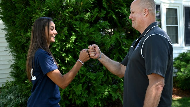 Framingham junior Sophie Albright and her father, Mark, demonstrate the special handshake they perform before her track meets. Albright won the All-State championship in the high jump last March.