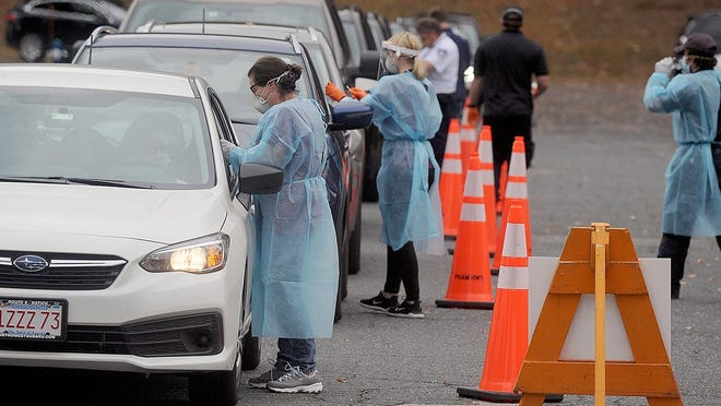 Health care workers wearing protective gowns and masks approach vehicles at the COVID-19 testing site at Walsh Middle School in Framingham in October.