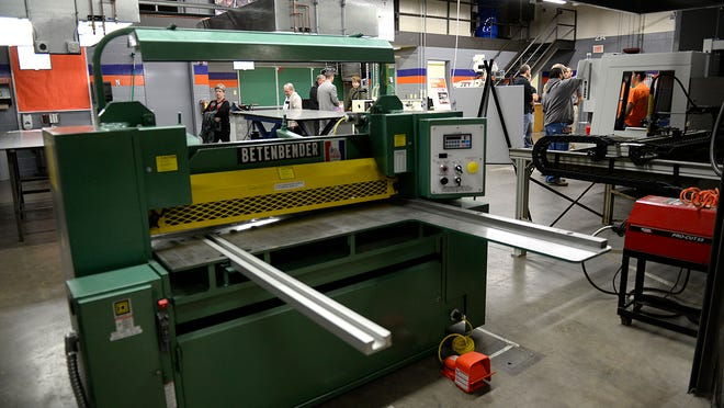People tour Bay Link Manufacturing on Tuesday at Green Bay West High School. The program is designed to provide high school students with real-world experience in manufacturing, engineering, marketing and business careers.