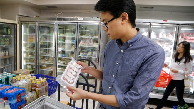 Journal & Courier reporter Wei-Huan Chen looks at a package of octopus as he searches for exotic Asian foods at Asia Oriental Market in West Lafayette.