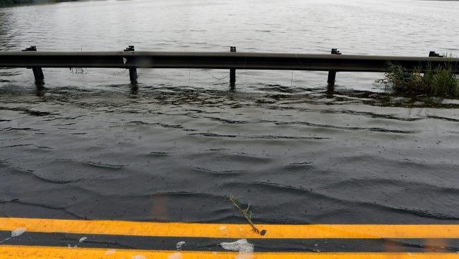 Water spills onto Del. 9 near Port Penn during high tide on Saturday.  WILLIAM BRETZGER/THE NEWS JOURNAL