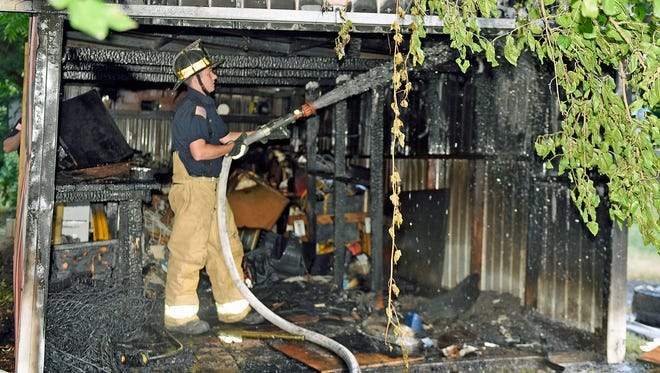 Chambersburg fireman Jeremy Heckman sprays hot spots at a shed fire around 4:30pm,Wednesday, Sept. 7, 2016, at an alley off King Street between 4th and Kennedy streets. The fire in a 20 x 40 ft. shed was quickly extinguished and the cause is under investigation.