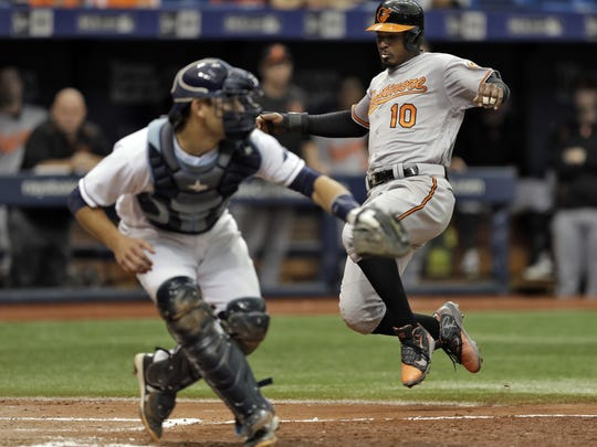 Baltimore's Adam Jones slides home ahead of the throw to Tampa Bay Rays catcher Luke Maile.