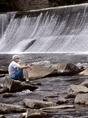 This file photo from May 29, 2013, shows Dave McCann fishing in the East Fork of the Stones River under the Walter Hill Dam.
