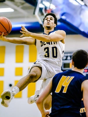 Jesse Tyler ,30, of DeWitt takes the ball to the basket as Avery McKinney ,14, of Haslett looks on during their game Friday February 19, 2016 in DeWitt.