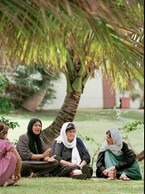 Kurdish refugee women evacuated with their families from Iraq sit and relax underneath a palm tree in Operation Pacific Haven on Guam in this March 18, 1997, file photo.