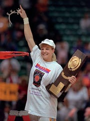 FILE - This March 31, 1996 file photo shows Michelle Marciniak, of Tennessee, holds the women's NCAA National Championship trophy after cutting the net and waving to the crowd after Tennessee defeated Georgia 83-65 in the finals of the NCAA women's basketball tournament in Charlotte, N.C. Brooke-Marciniak played for Pat Summitt on Tennessee's 1996 national championship team and now serves as a board member on her former coach's foundation. She will honor Summitt once again this week as she joins a group of cyclists riding 1,098 miles - one mile for each of Summitt's career wins - to raise money and awareness in fighting Alzheimer's disease. (AP Photo/Amy Sancetta, file)