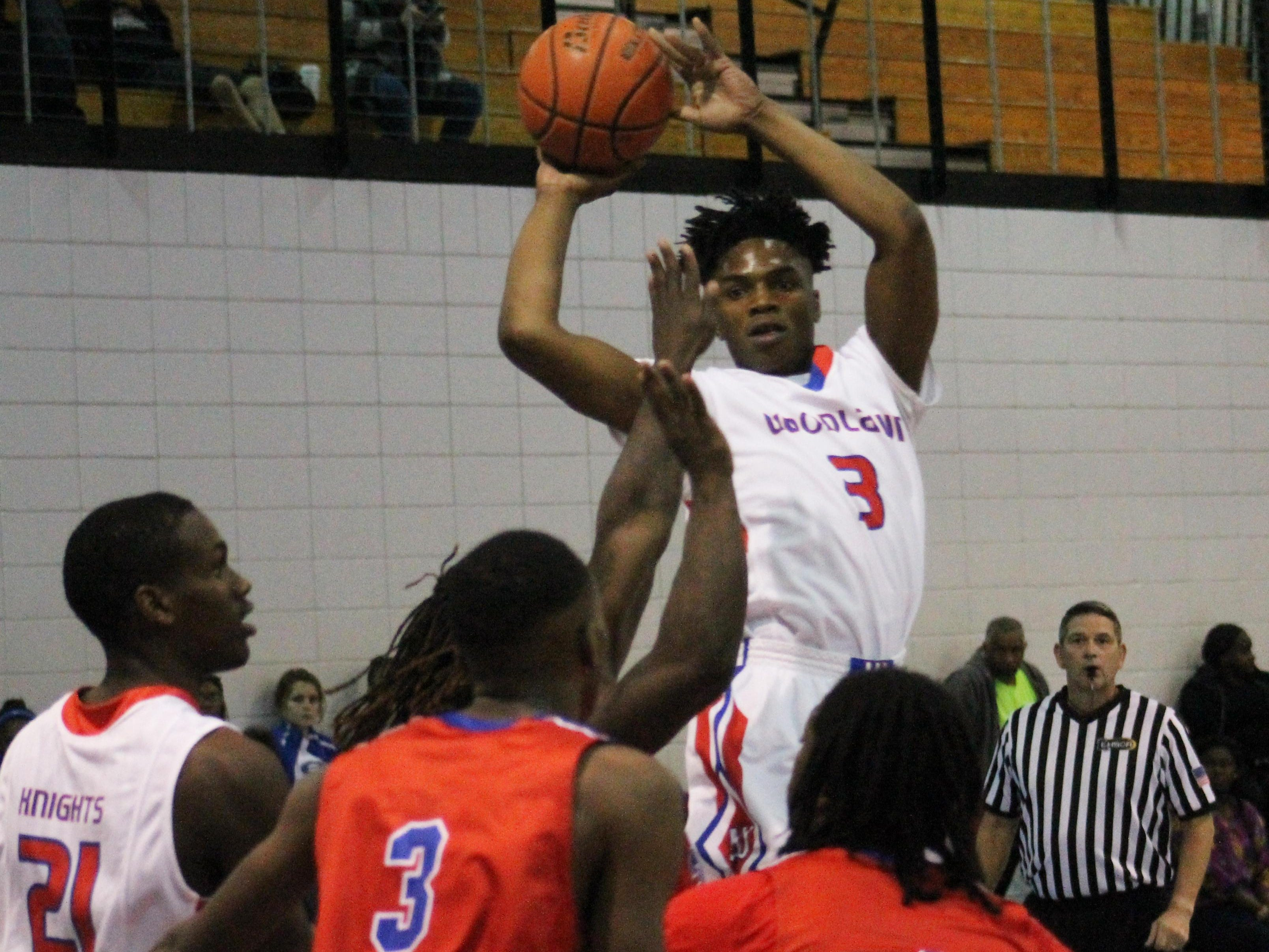 Willie Reed (3) jumps to pass for Woodlawn against Evangel during Thursday night's boys basketball game in Minden.