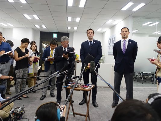Jean-Christophe Rolland, center, president of the Swiss-based International Rowing Federation, accompanied by Koji Murofushi, right, sport director for the 2020 Tokyo Organizing Committee, speaks to the press following his meeting with 2020 Tokyo Organizing Committee Deputy Director Yukihiko Nunomura in Tokyo Monday, Oct. 3, 2016. Rolland says he is seeking clarification from Tokyo officials after a city advisory panel recommended moving the 2020 Olympics rowing competition far from the Japanese capital to save money. He said the reports of a possible venue change had come as a surprise. (AP Photo/Mari Yamaguchi)