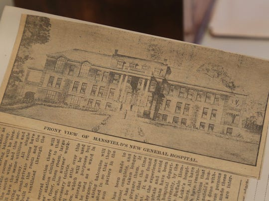 A newspaper clipping shows a drawing of Mansfield General Hospital. The hospital has changed greatly in its hundred years of existence, with several additions and expansions to the original building.