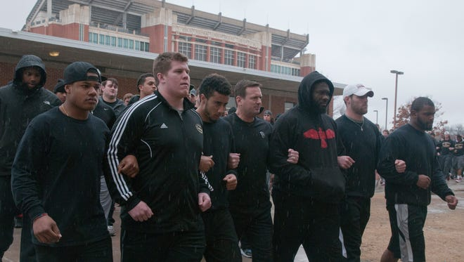 The University of Oklahoma football team and coaches walk into practice wearing all black in protest of the Sigma Alpha Epsilon fraternity at the University of Oklahoma on Monday, March. 9, 2015. The Sigma Alpha Epsilon fraternity has been banned from campus after  f several members of the fraternity took part in a racist chant caught on video.