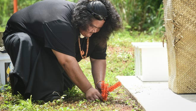 "Jeremy Cepeda of the I Fanlalai'an oral history project plants a ceremonial niyoron, or orange blossom, at the site of the Dandan Reburial Memorial in Inarajan on Friday, July 17. ""It doesn't matter where you go, we are always standing on the bones of those who came before us,"" said Cepeda."