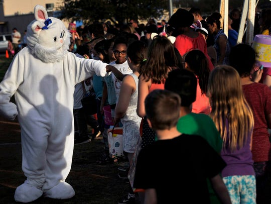 The Easter Bunny fist-bumps young fans as they wait for the beginning of the city of Abilene's annual Evening Easter Egg Hunt Saturday, sponsored by the Parks and Recreation Department.