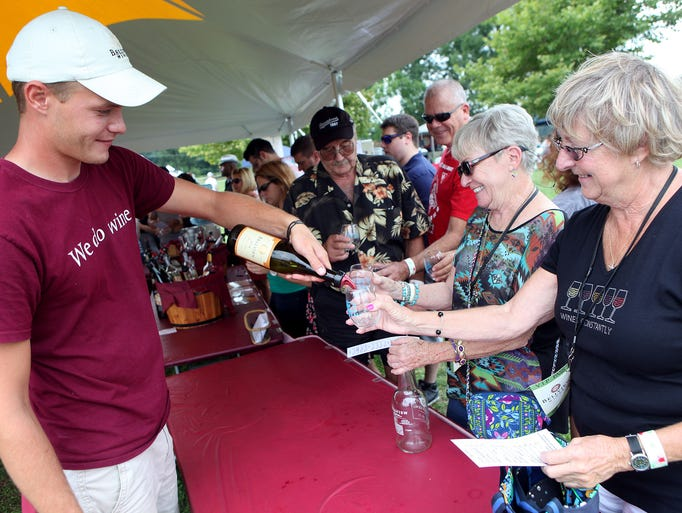 Winery employee Nick Serata of Bridgeton, left, serves the Bellview Viognier to Betty Lemley of Logan Township, and Nancy Bergested of Barnegat, from left, during the Bellview Seafood Festival at Bellview Winery in Landisville, Sunday, Aug. 17, 2014.  Staff Photo/Sean M. Fitzgerald