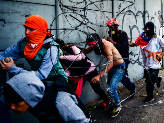 Opposition demonstrators run during clashes with riot