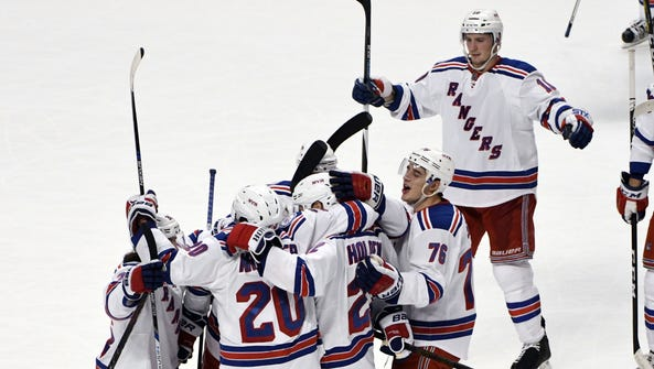 The Rangers celebrate the game-winning goal by defenseman