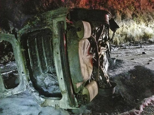 This Aug. 3 photo from the Hoopa Fire Department shows a Humboldt County Sheriff's Department patrol car after it was struck by a falling bear and then hit an embankment, rolled onto its side and burst into flames, near Hoopa, Calif., in Northern California. The deputy managed to escape without serious injury. (Rod Mendes/Hoopa Fire Department via AP)