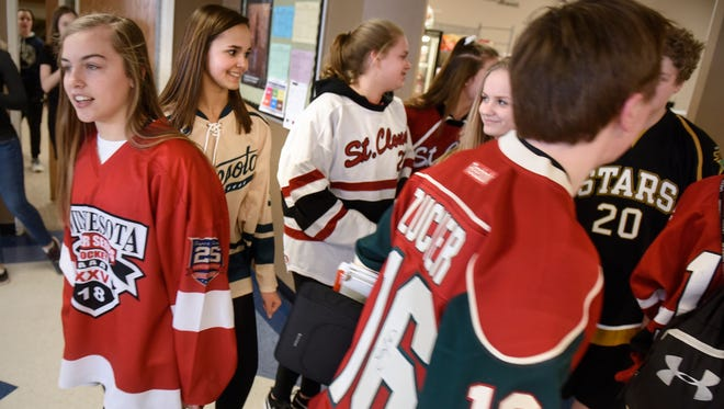Students wear hockey jerseys in tribute to the families of those affected by the deaths of Humboldt Broncos junior hockey players during lunch at Cathedral High School Thursday, April 12, in St. Cloud.