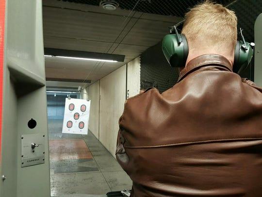 Paul Sadler practices shooting her pistol at a gun