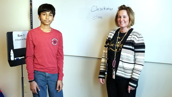 Jashun Paluru, left, stands with Battle Ground Middle School Principal Jodi Day, right, in front of Paluru's two of favorite words.