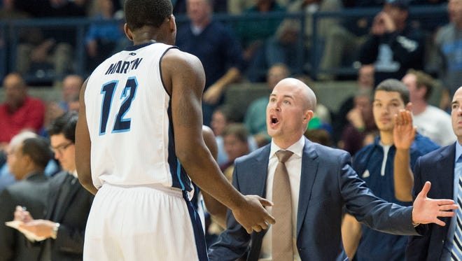Rhode Island assistant coach Luke Murray (right) talks to Rams forward Hassan Martin in November of 2014.