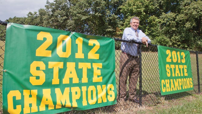 From 2014: Tony Karcich poses next to one of the championship banners at the school. Karcich is retiring from St. Joseph's as athletic director at the end of the school year.