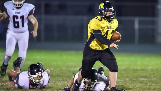 """In this Thursday, Oct. 27, 2016 photo, Mitchell High senior Tayler Reichelt (43), known as the """"T-Man,"""" races past a pair of Sturgis defenders on a 58-yard touchdown run during a high school football game in the first round of the Class AA state playoffs in Mitchell, S.D. His teammates mobbed Reichelt, who has Down syndrome, after he scored."""